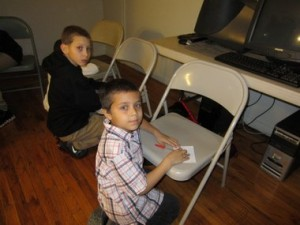 Jeremiah Sabageau, 9, on the left, and Giovanni Mendez, 8, get ready for a 'Boys to Men' talk at the Springfield Housing Authority's John J. Duggan Apartments. Photo by (Mary Ellen Lowney)